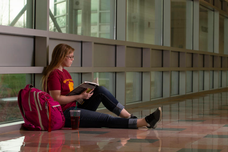 Nursing student sitting in a hallway next to a backpack