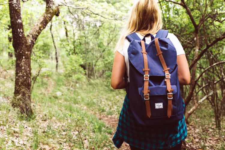 Student wearing a Herschel backpack walking in the woods