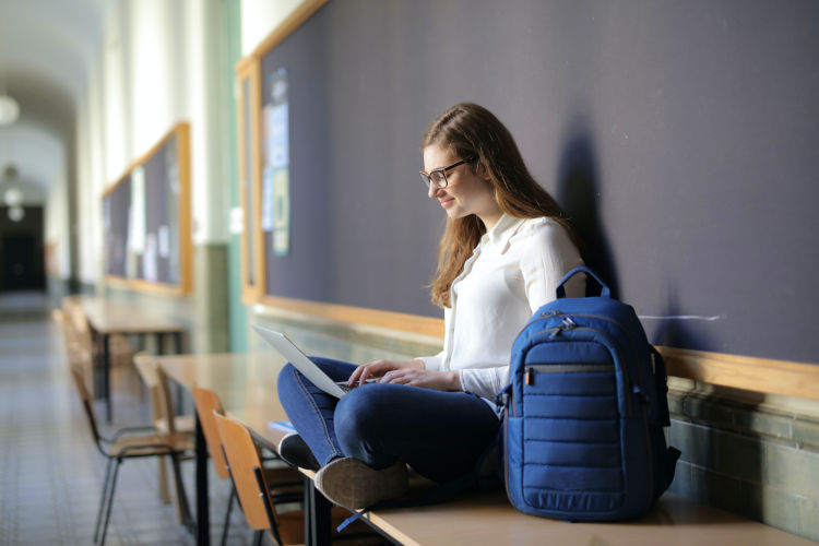 Student sitting in a hallway with a nursing school backpack